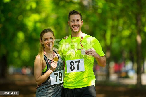 smiling young woman with gold medal and happy man with silver medal after finishing running event