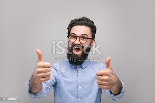 istock Successful happy hipster showing thumbs u 924969670