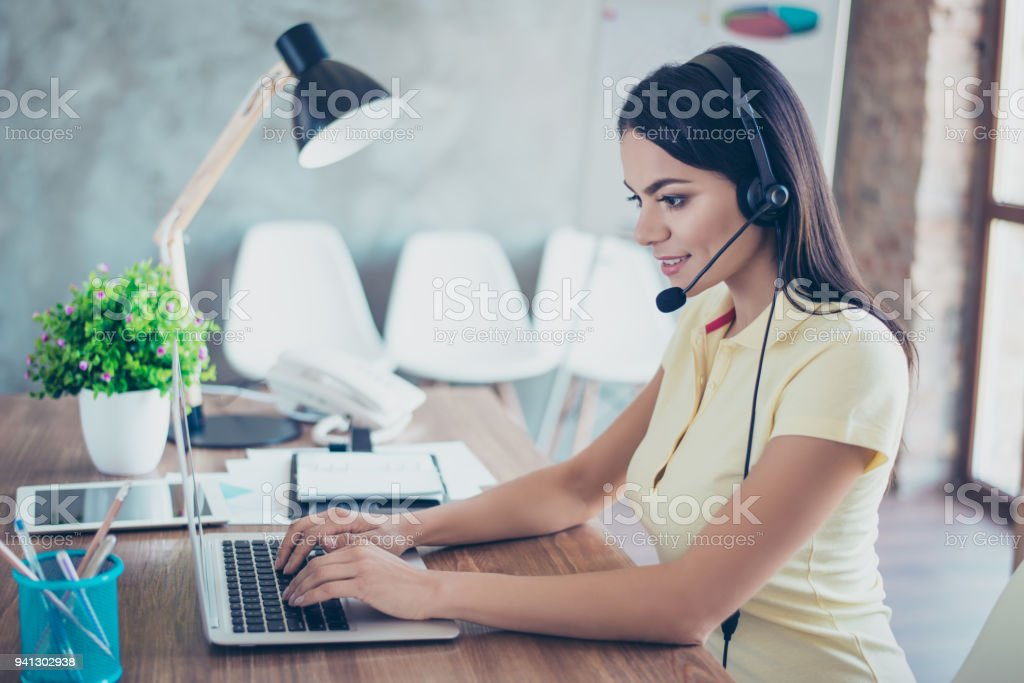 Successful happy young hispanic businesswoman is talking to customer with headset on and putting data in her computer stock photo