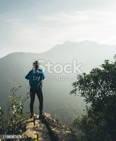 Successful hiker enjoy the view on sunrise mountain top cliff edge