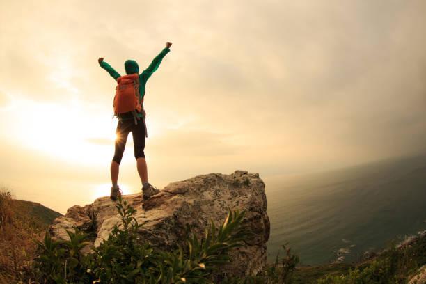 successful hiker hiking on seaside mountain peak stock photo