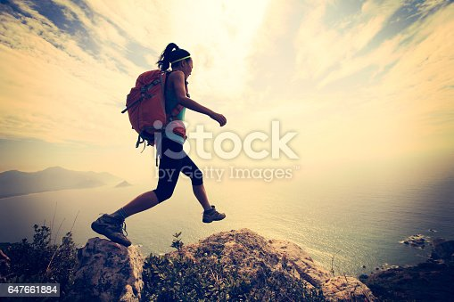 successful hiker jumping on seaside mountain peak rock