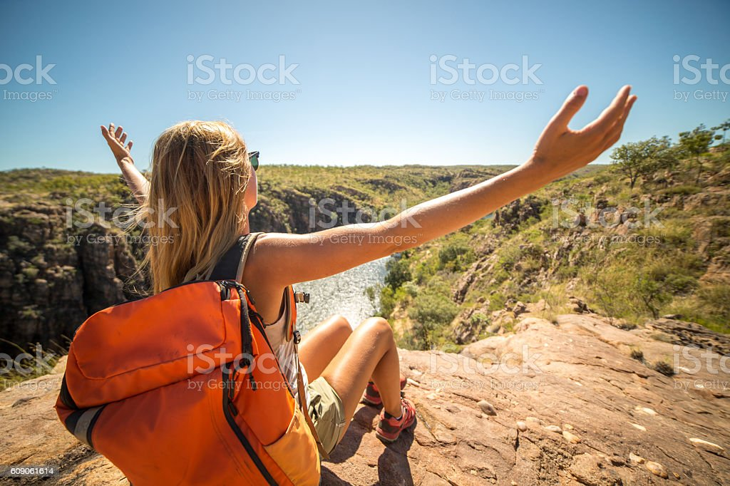 Young woman hiking sits on cliff and looks at view arms outstretched....