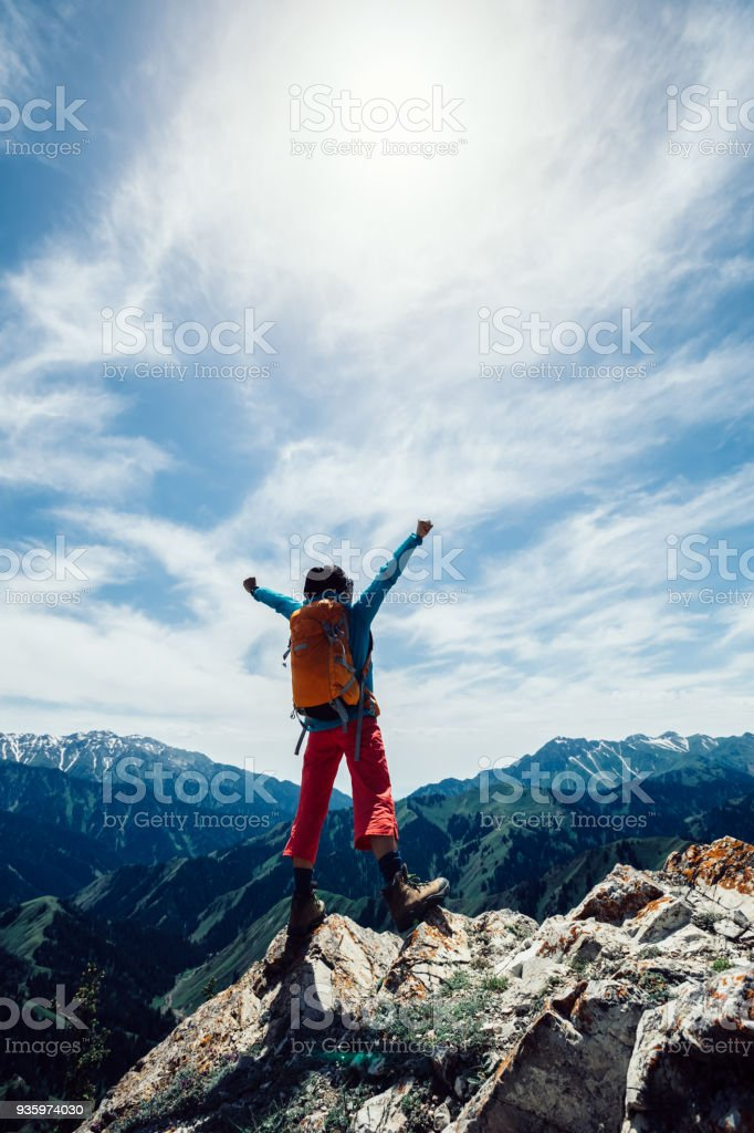 successful Hiker outstretched arms stand at cliff edge on mountain top – zdjęcie