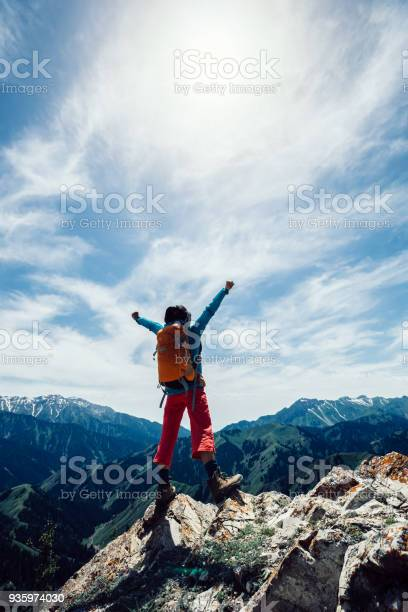 Photo of successful Hiker outstretched arms stand at cliff edge on mountain top