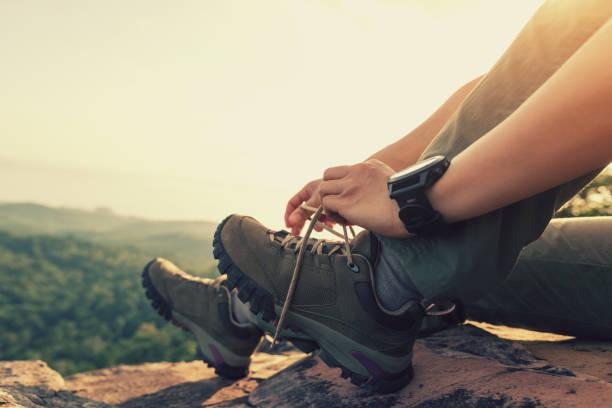 Erfolgreiche Wanderer sitzen und an der Bergspitze die Schuhputzel binden – Foto