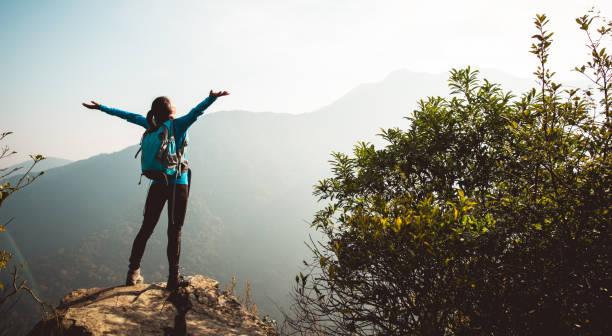 Erfolgreicher Wanderer mit ausgestreckten Armen auf Sonnenaufgangsberg – Foto