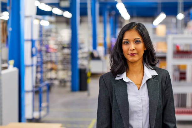 Successful indian female entrepreneur standing in factory stock photo