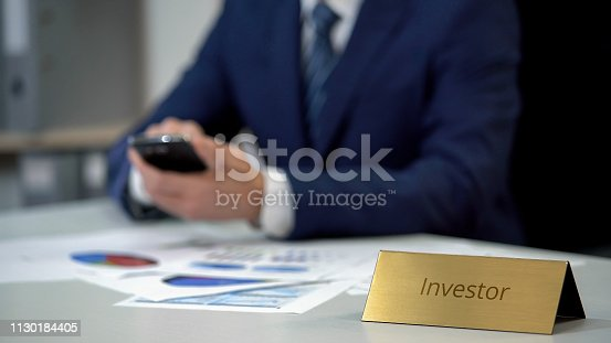 1130184417 istock photo Successful investor using mobile phone, checking investment project results 1130184405