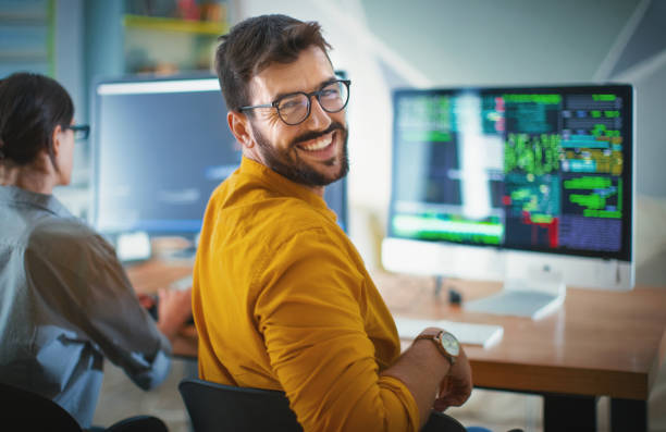 Successful IT developer. Closeup over the shoulder view of a cheerful mid 20's software developer at the office smiling to the camera. His female coworker is next him, still focused and working. looking over shoulder stock pictures, royalty-free photos & images