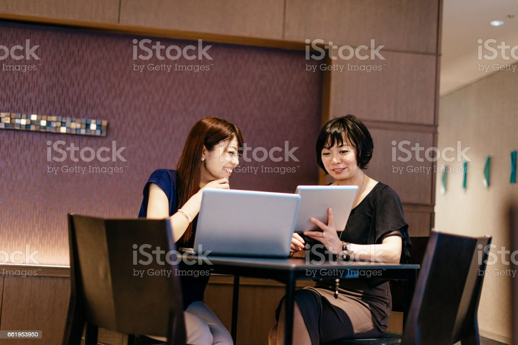 Successful Japanese businesswomen having meeting, discussing projects and cooperation royalty-free stock photo