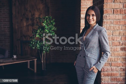 istock Successful lady standing in a gray checked suit holding her hands in pockets looking into the camera leaned against a brick wall on comfort workplace 1059107556