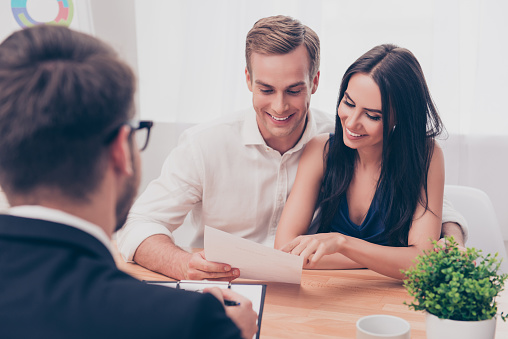 938640610 istock photo Successful lawyer giving consultation to family couple about buying house 951092116