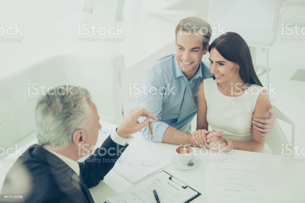 Successful lawyer giving  to family couple keys of new house stock photo