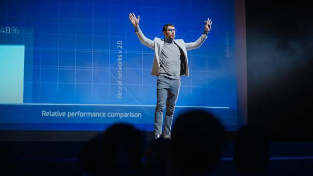 framgångsrika manliga högtalare får på scenen, hälsar publik och gör presentation av den tekniska produkten, visar infographics, statistik animation på skärmen. liveevent / uppstartskonferens - graphs animation bildbanksfoton och bilder