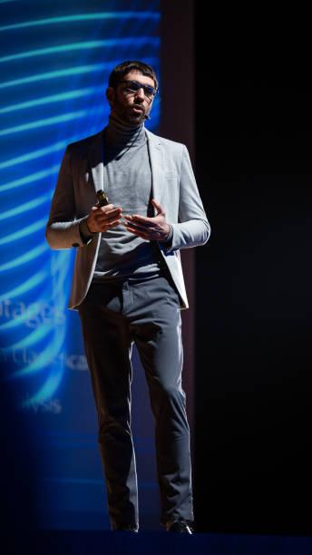 framgångsrika manliga högtalare står på scenen, hälsar publik och gör presentation av den tekniska produkten, visar infographics, statistik animation på skärmen. uppstartskonferens. vertikal bild. - graphs animation bildbanksfoton och bilder