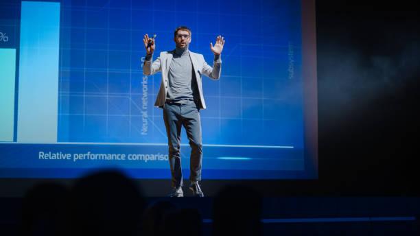 framgångsrika manliga högtalare står på scenen, hälsar publik och presentation av den nya produkten, visar infographics, statistik animation på skärmen. live event / device release / start-up konferens - graphs animation bildbanksfoton och bilder