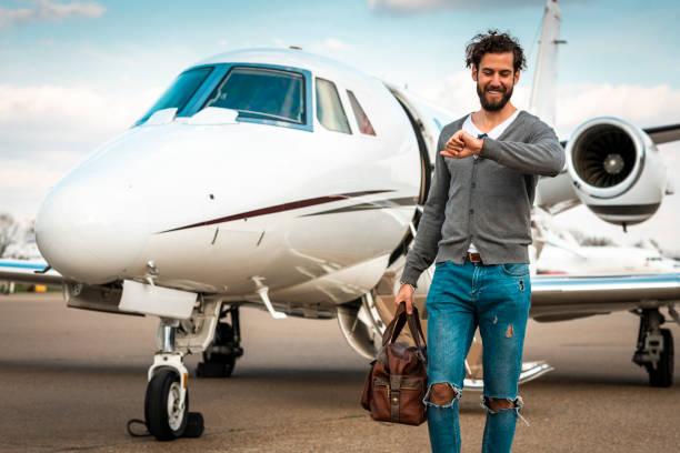 Erfolgreicher Mann, der die Zeit überprüft, während er von einem Privatflugzeug entfernt ist, das auf einem Taxistand geparkt ist – Foto