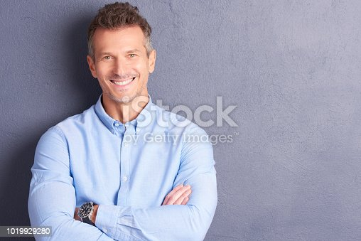 Portrait of middle aged businessman wearing shirt and looking at camera while standing at grey background.
