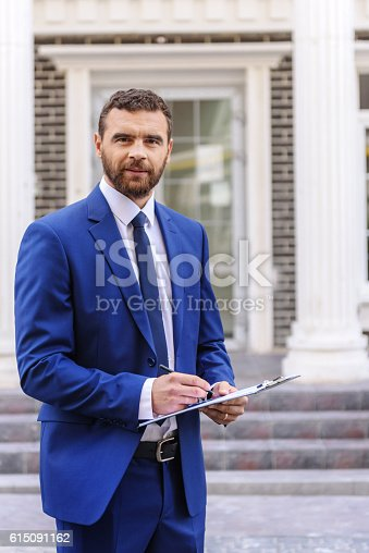 istock successful man standing outdoors 615091162