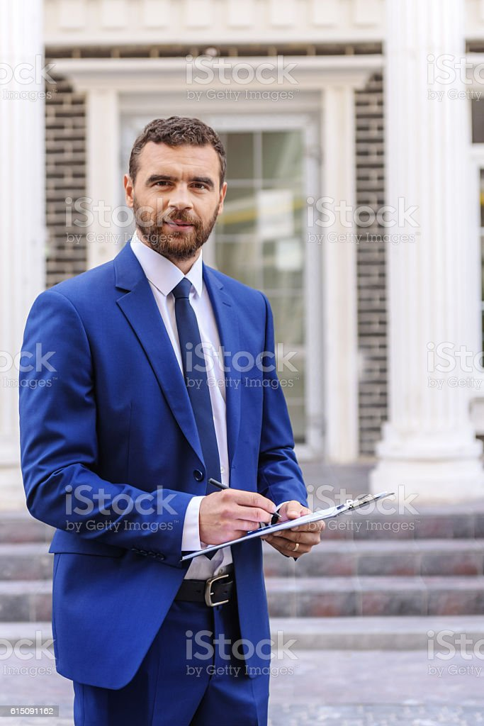 successful man standing outdoors stock photo