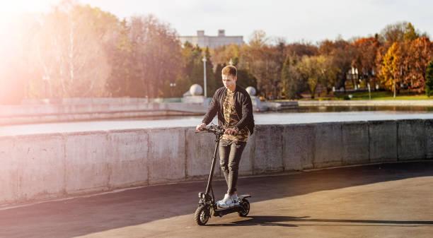Erfolgreicher Mann mit technologischem, umweltfreundlichem Elektro-Kick-Scooter. Konzept mit Kopierraum an der Straße in einer Stadt – Foto