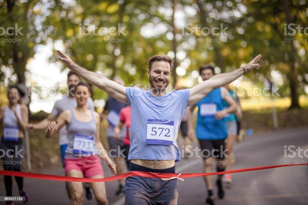 成功的馬拉松賽跑者橫渡終點線在自然。 - 免版稅Sportsperson圖庫照片