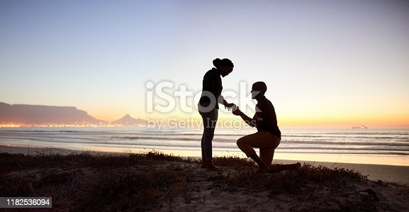 Silhouette of young man making proposal wearing engagement ring to his girlfriend at the beach in evening