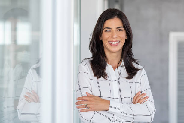 Successful mature business woman looking at camera Portrait of middle aged businesswoman in modern office looking at camera. Confident business woman with arms crossed standing while leaning against glass wall. Proud brunette woman smiling in formalwear with copy space. latin american and hispanic ethnicity stock pictures, royalty-free photos & images