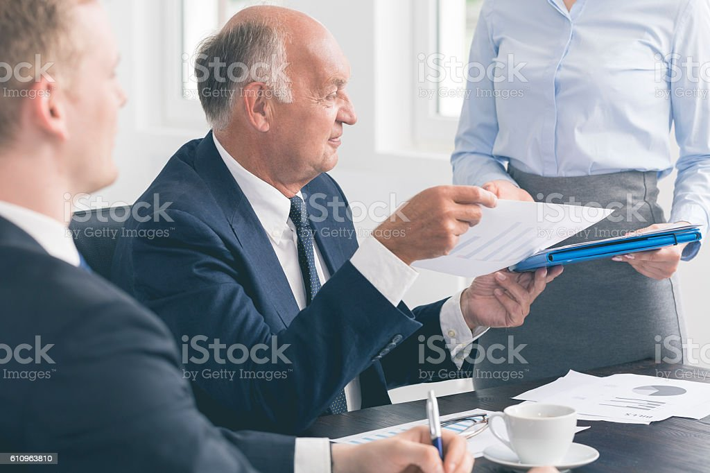 Successful mature businessman assisted by a devoted secretary stock photo