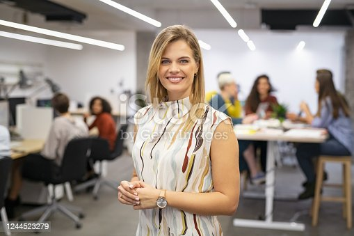 Portrait of beautiful business woman looking at camera while business team working in background. Executive woman standing in office while looking at camera. Portrait of happy and smiling creative businesswoman standing in front of co-workers at office.