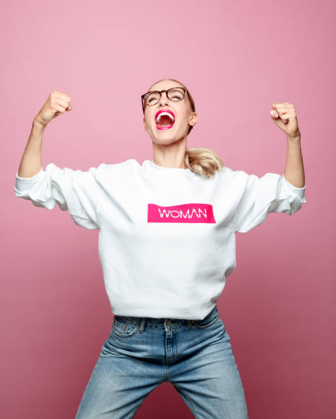 Successful mid adult woman screaming Successful woman clenching fists. Beautiful strong female is screaming against pink background. She is wearing white t-shirt. win stock pictures, royalty-free photos & images