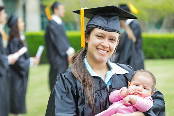 Successful mom holding baby after graduation ceremony stock photo