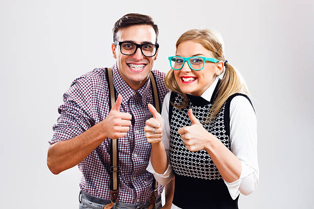 Successful nerds Happy nerdy couple showing thumbs up. nerd stock pictures, royalty-free photos & images