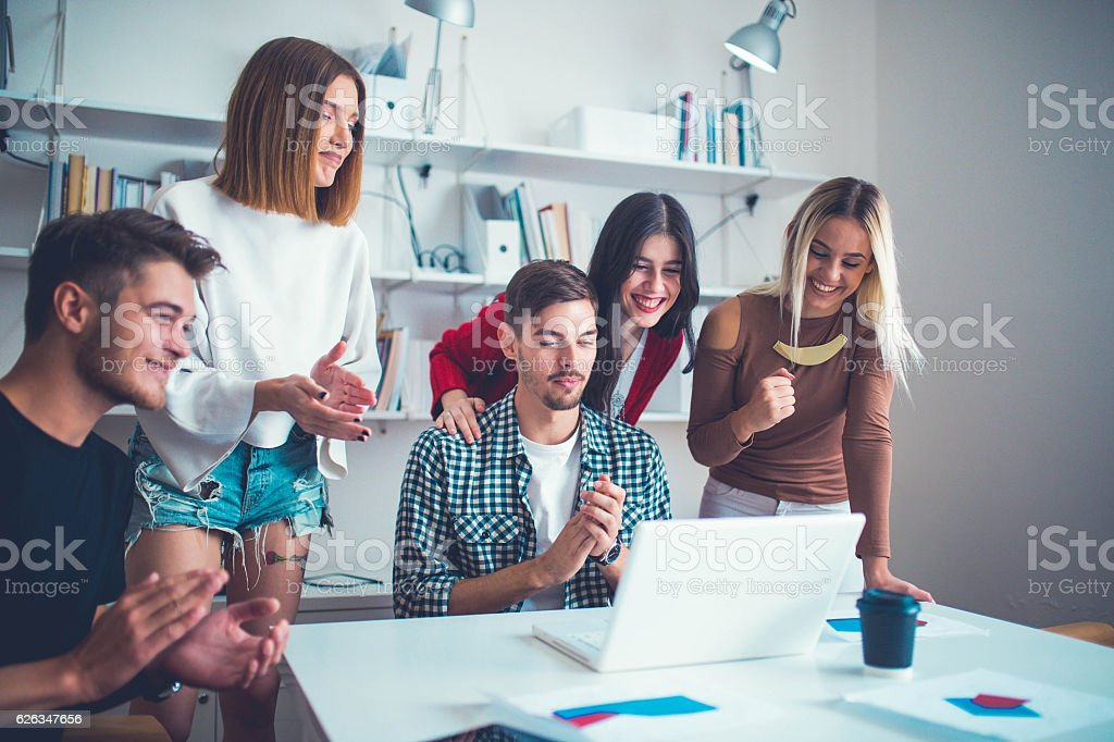 Group of young successful people working together in office. They are...