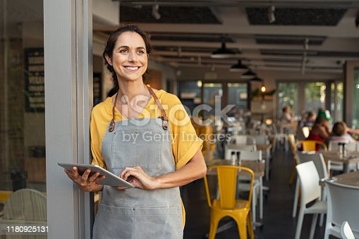istock Successful owner standing at cafe entrance 1180925131