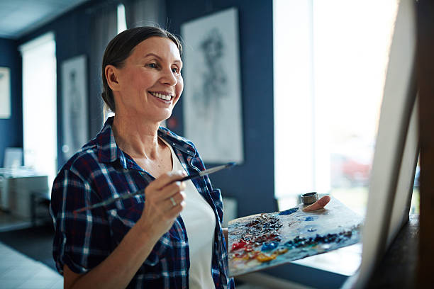 Successful painter Happy elderly woman looking at her painting in art studio hobbies stock pictures, royalty-free photos & images