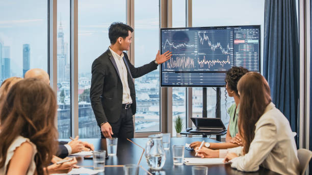 Successful presentation. Elegant man explaining growth of sales graph, reporting about good result, motivating workers. Multi ethnic team in board room stock photo