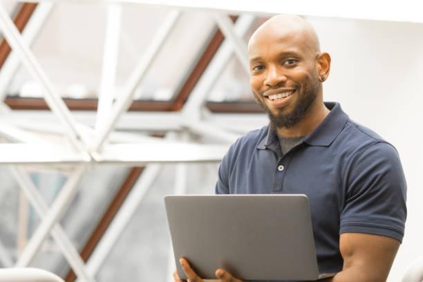 succesvolle professionele man van afro-amerikaanse afstammeling - foto's van business people on computer stockfoto's en -beelden