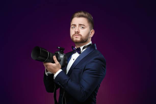 successful professional photographer in tuxedo use dslr digital camera on - dunkle flecken entferner stock-fotos und bilder