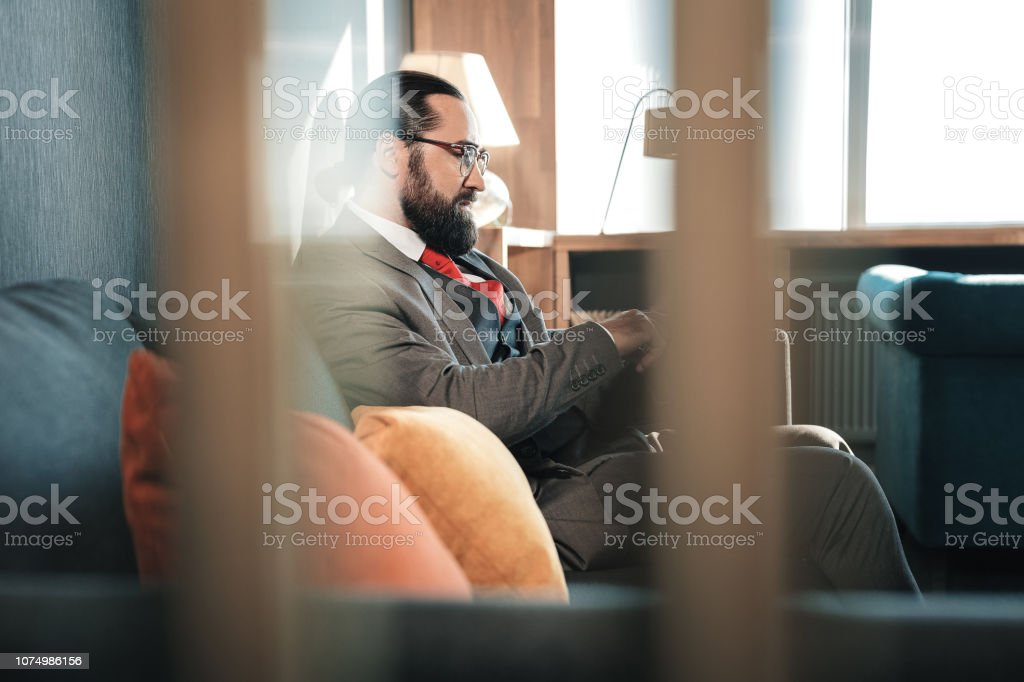 Hotel room. Successful prosperous man wearing glasses sitting in his...