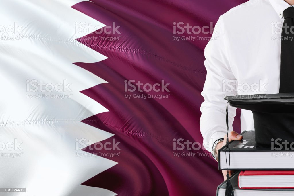 Exitoso concepto de educación estudiantil de Qatar. Sosteniendo libros y gorra de graduación sobre el fondo de la bandera de Qatar. - foto de stock