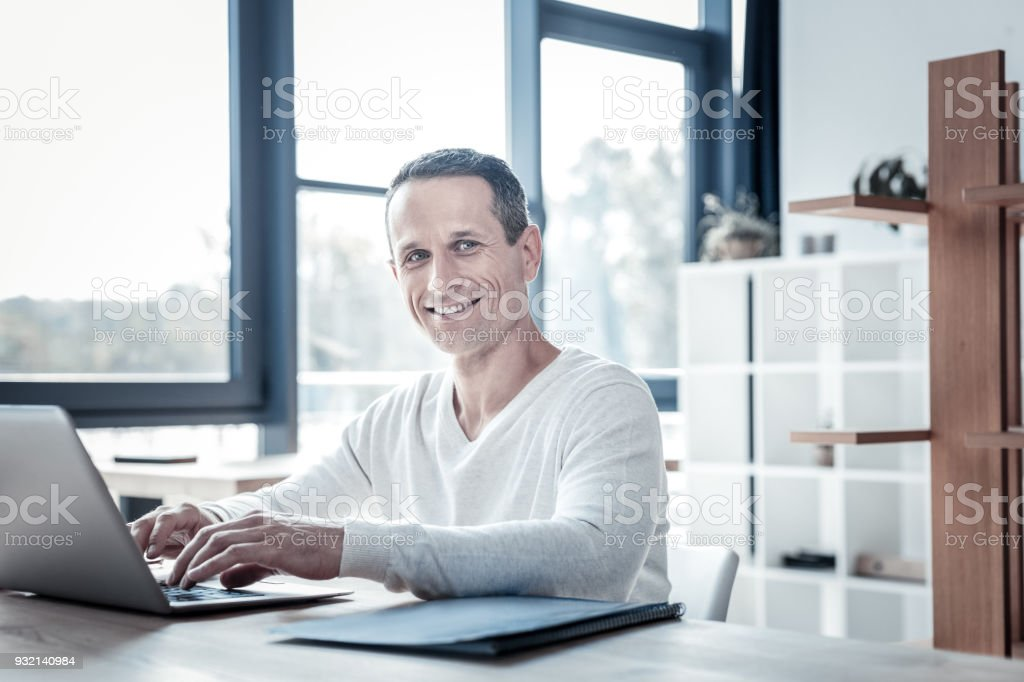 Successful qualified man smiling and using the laptop. stock photo