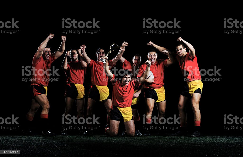 Rugby team celebrating their success. One of rugby players is holding...