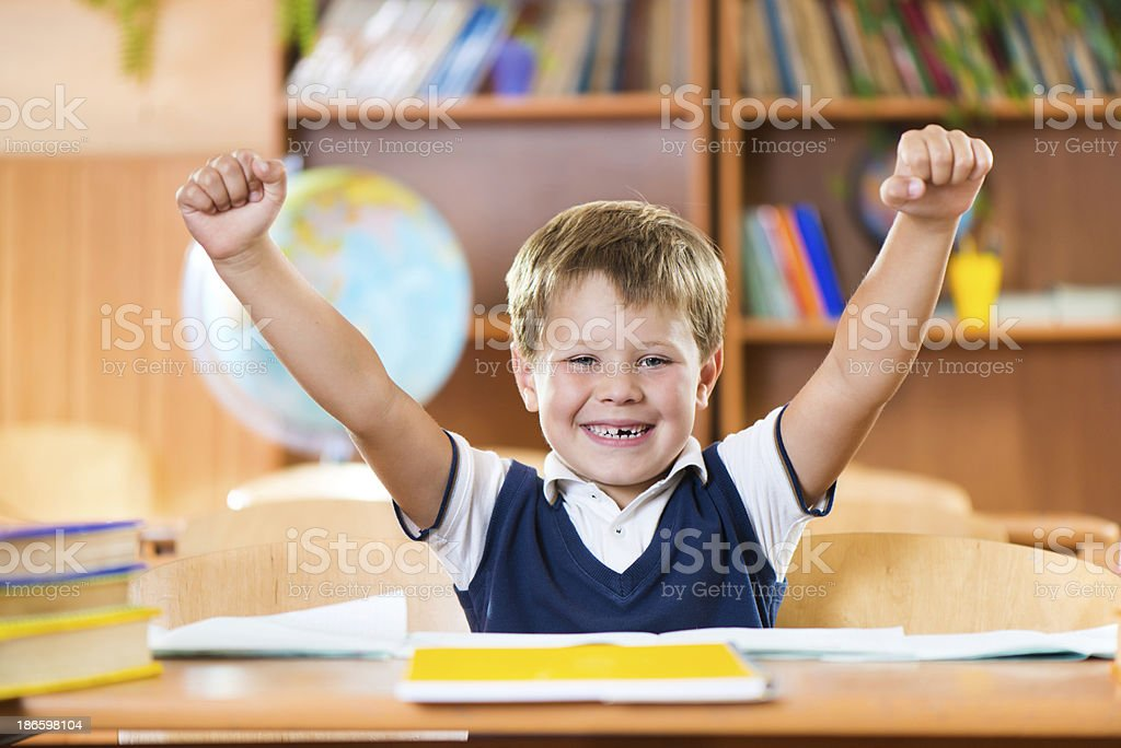Successful schoolboy with hands up sitting at desk stock photo