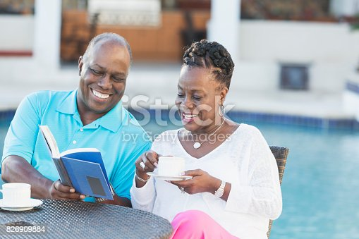 istock Successful senior African-American couple by pool 826909884