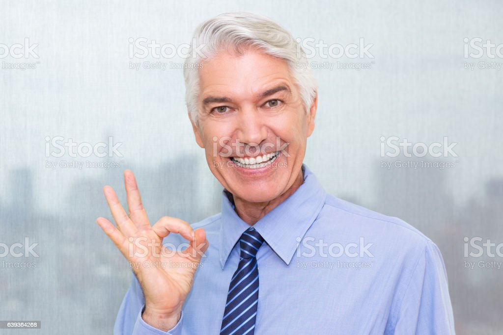 Successful senior businessman showing ok sign stock photo