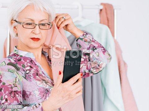 1133515238 istock photo successful senior woman fashion boutique business 1133515235