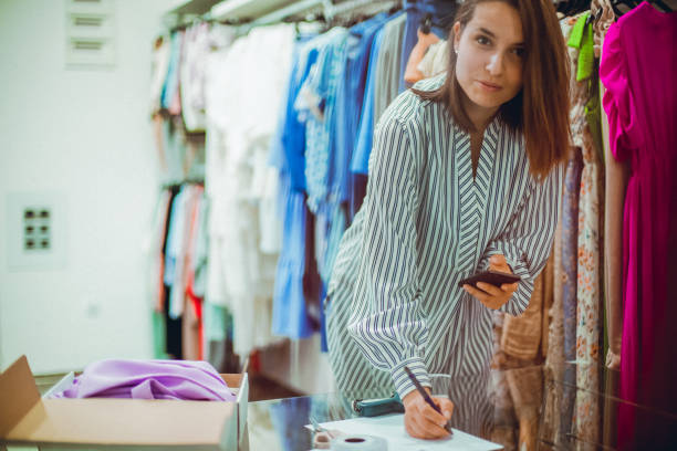 Successful shopping A woman is in the clothes store. She is looking at the camera while copying something from her phone to the documents that she is fulfilling. signature collection stock pictures, royalty-free photos & images