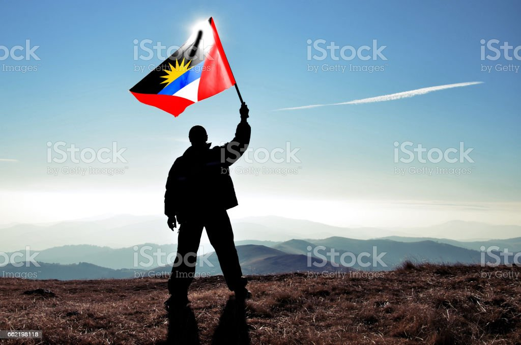 Successful silhouette man winner waving Antigua and Barbuda flag on top of the mountain peak stock photo